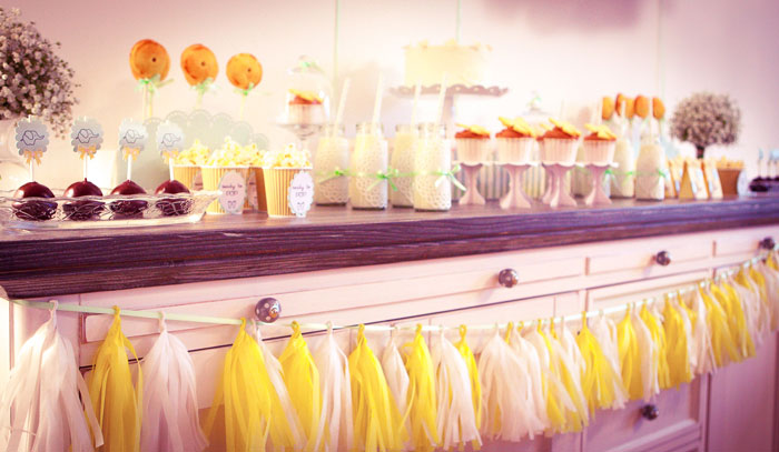 Eine selbstgebastelte Tasselgirlande in Gelb und Weiß für die neutrale Baby Shower