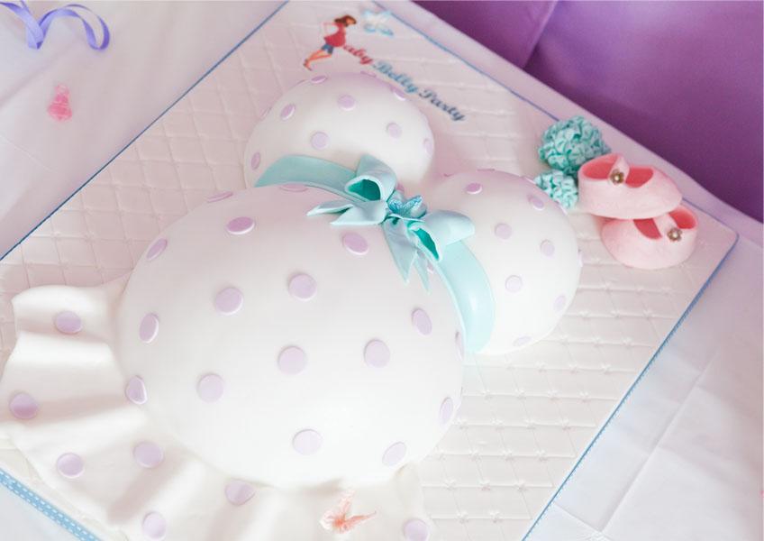 Babybauch-Torte in Weiß mit süßer Schleife in hellem Türkis