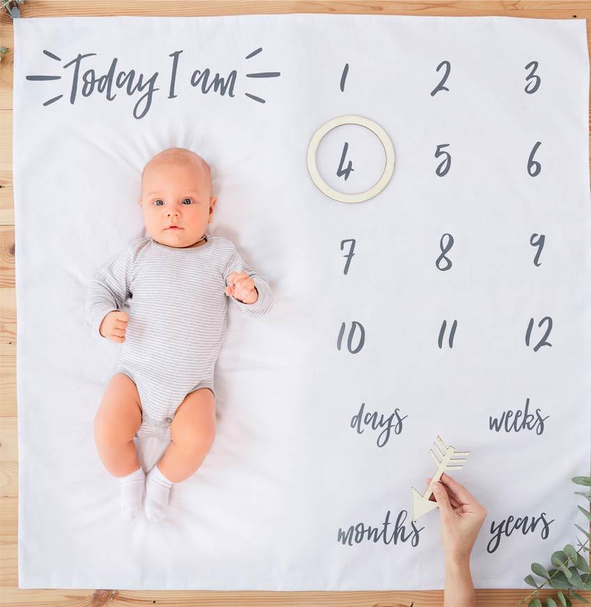 Schöne Foto-Idee: Mit der Meilenstein-Decke halten die Eltern die spannende Entwicklung ihres Babys fest