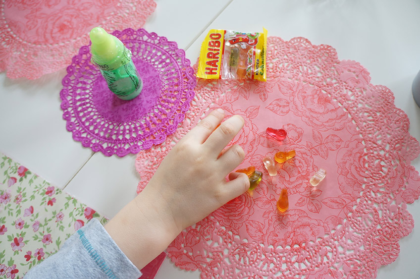 Sei kreativ und nimm bunte Doilies als schnelle und leichte Tischdeko für die Babyparty mit Kindern