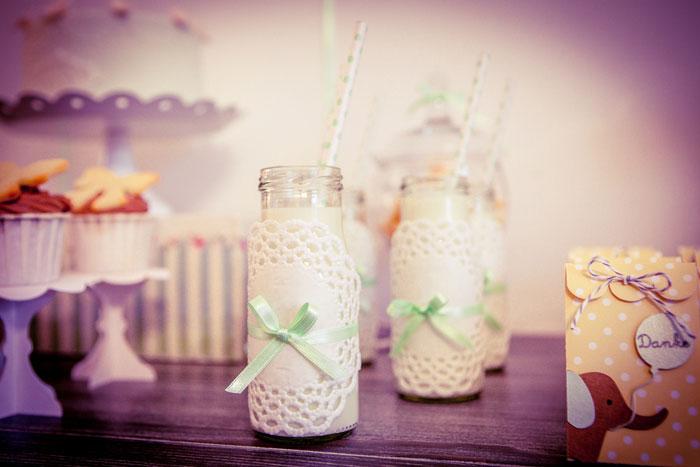 Milchfläschchen zur Babyparty mit kleinen Doilies und Schleifen verziert