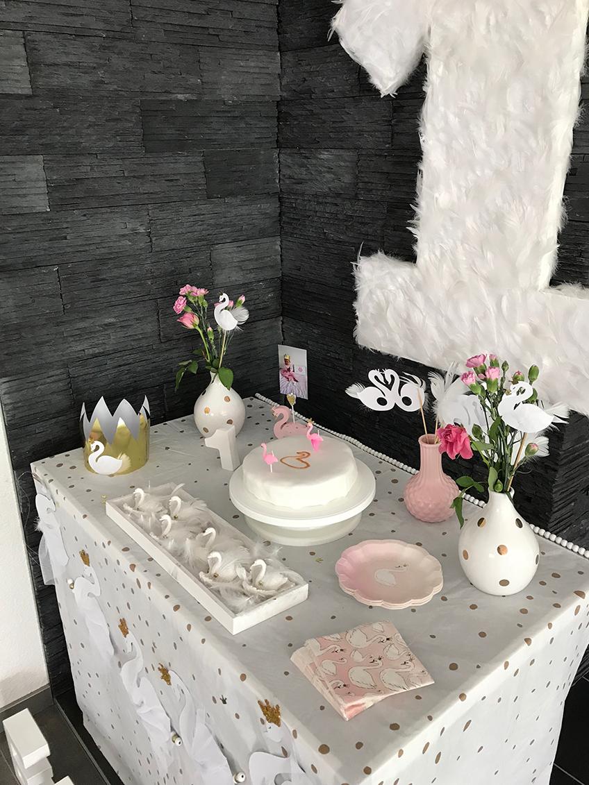 Das Märchentier Schwan bietet viel Anreiz für eine wunderschöne Geburtstagsdeko mit weißen Federn, Blumen und sanften Farben © eminecreative