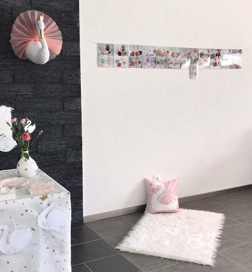 Auf dem Boden gibt es eine kuschelig weiße Decke, die an Schwanengefieder erinnern soll, dazu ein schönes Motiv-Kissen und eine Fotowand, die die Entwicklung der kleinen Schwanenprinzessin zeigt © eminecreative