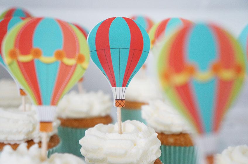 Wolken auf Muffins und Picks in Form eines Heißluftballons