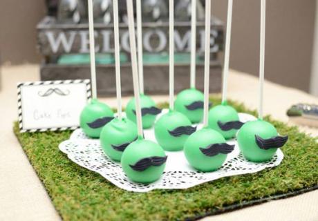 Grüne Cake Pops mit kleinen Schnurrbärten