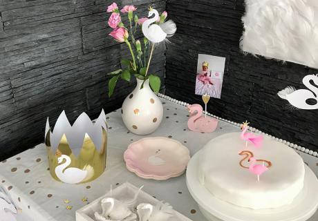 Der Schwan-Geburtstagskuchen hinter dem Schwanensee - mit rosafarbenen Schwänen, die nur ganz zufällig Flamingos ähneln :) Goldene Tupfer und Kronenkonfetti runden das Bild ab © eminecreative