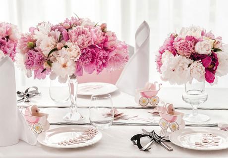 Frische Blumen in Pink und kleine Baby-Symbole für die Taufe kleiner Mädchen